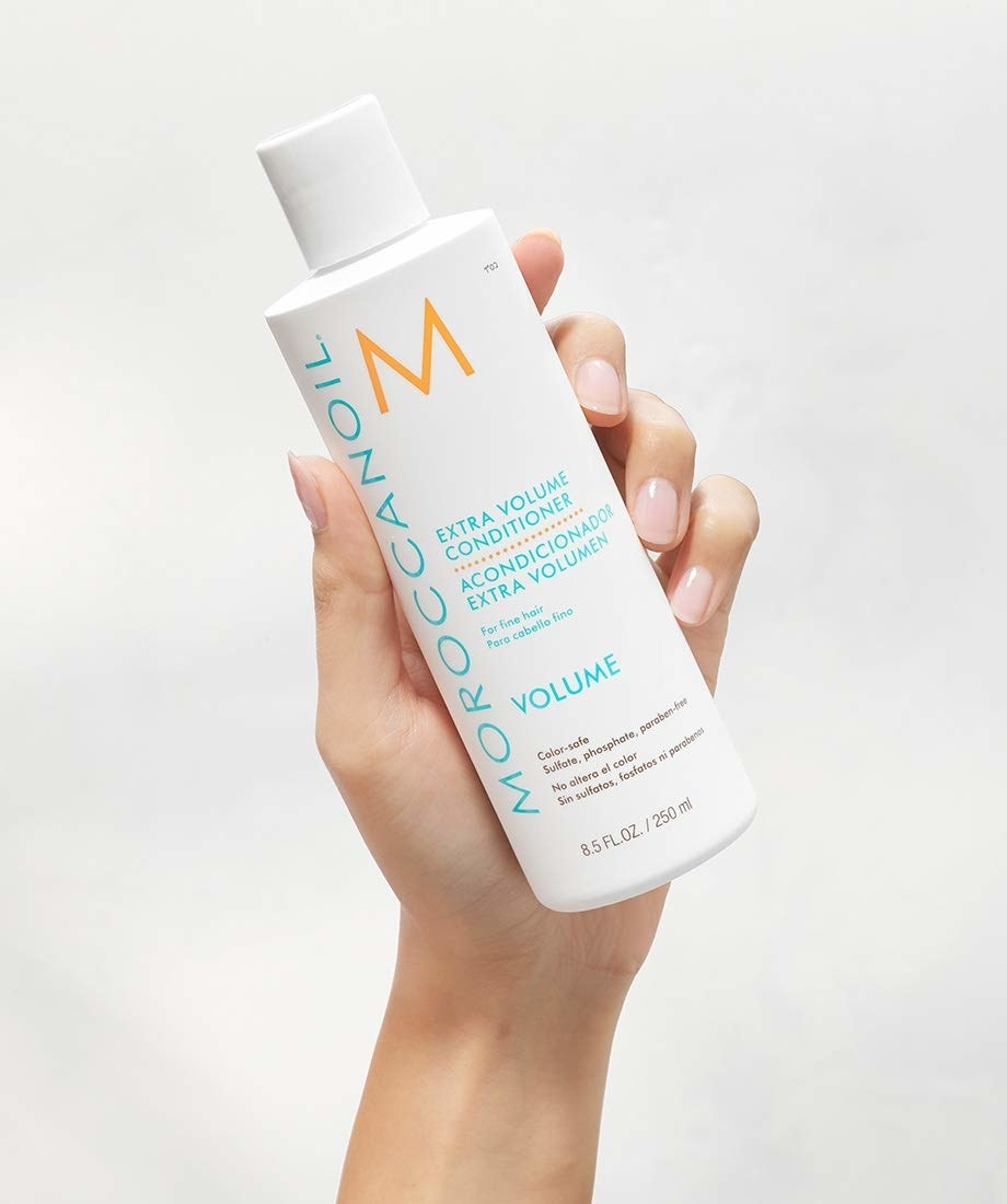 "hand holding white bottle with white cap labeled ""moroccanoil"" in blue text on the side"