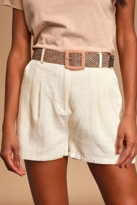 Closeup of model wearing high-waisted linen shorts worn with a belt