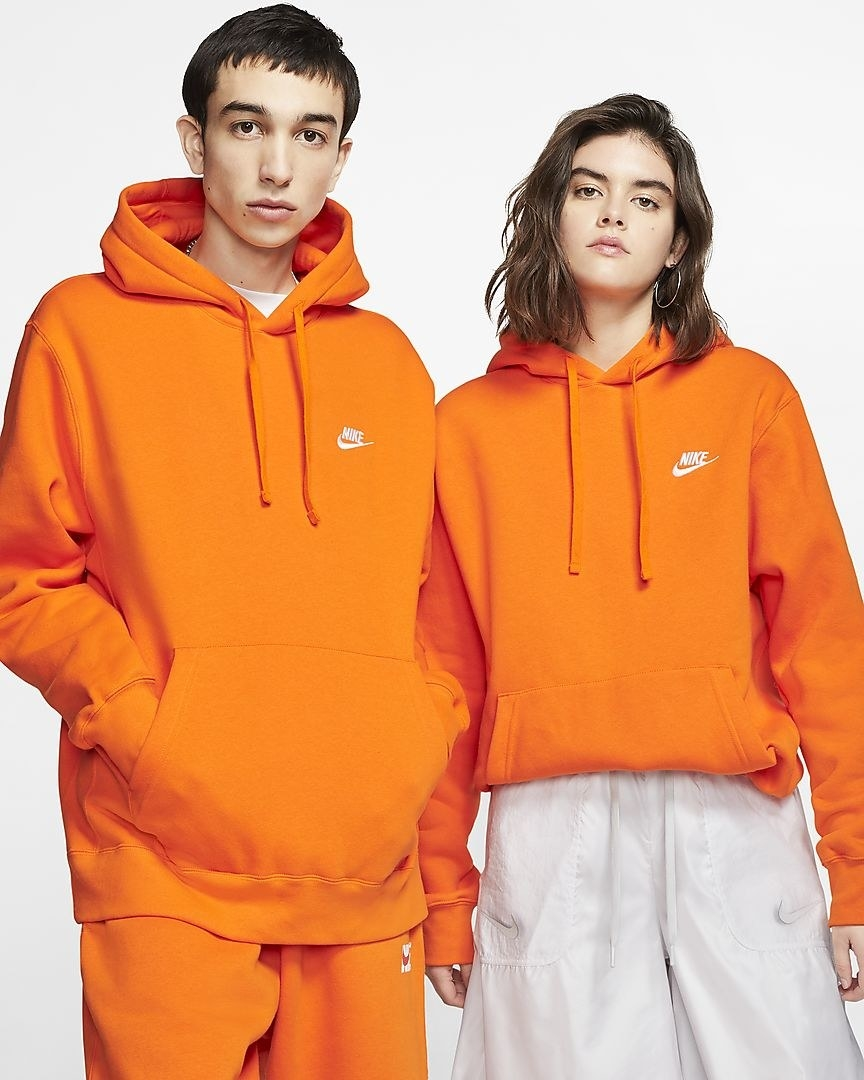 Two models, both wearing the hooded sweatshirt in bright magma orange