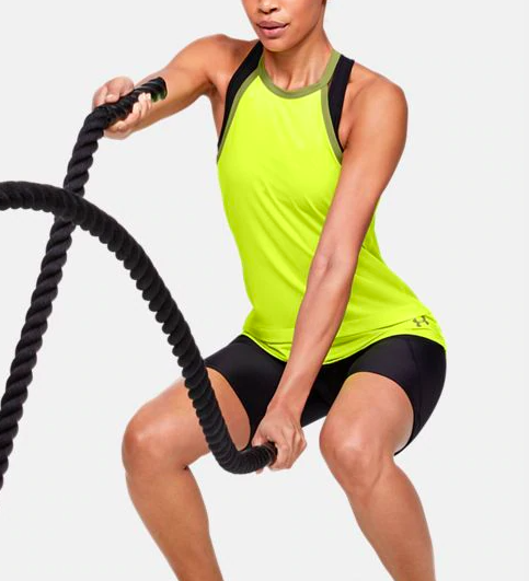 Woman wearing the sport tank in neon green and exercising with battle ropes