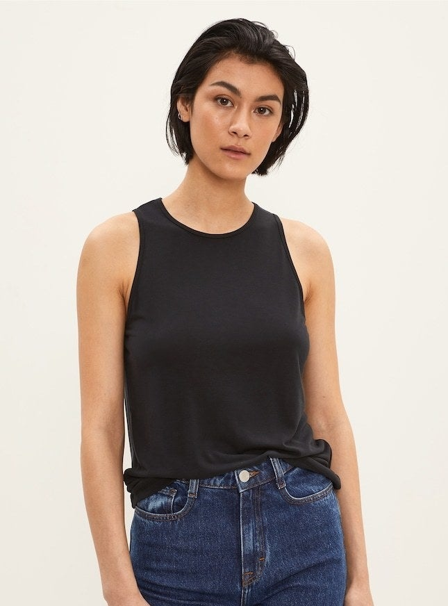 model in a black high-neck tank french tucked into high waisted jeans