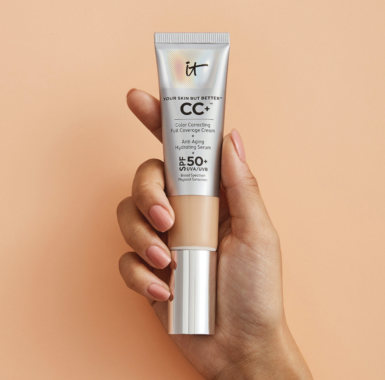 A hand holding a tube of the CC cream