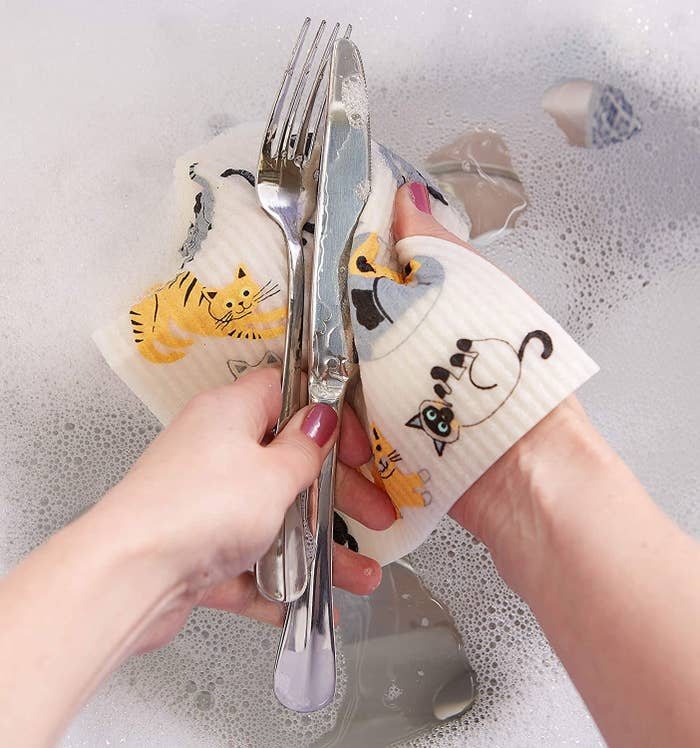 A person washing a knife and fork with a square-shaped Swedish dish cloth with happy cats printed on it.