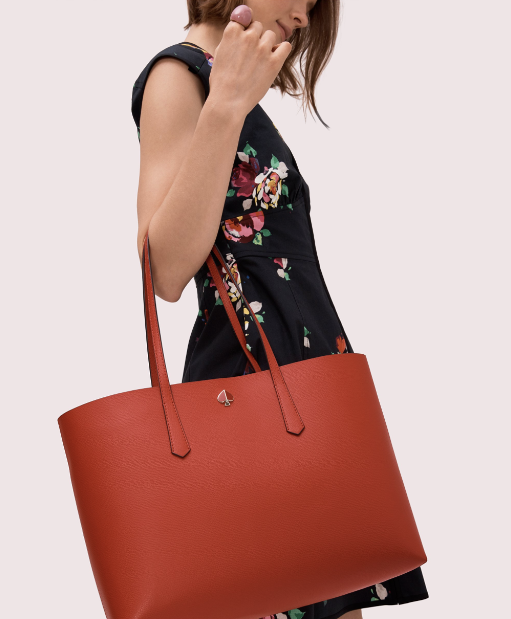 Model holding red tote bag in the crux of her arm