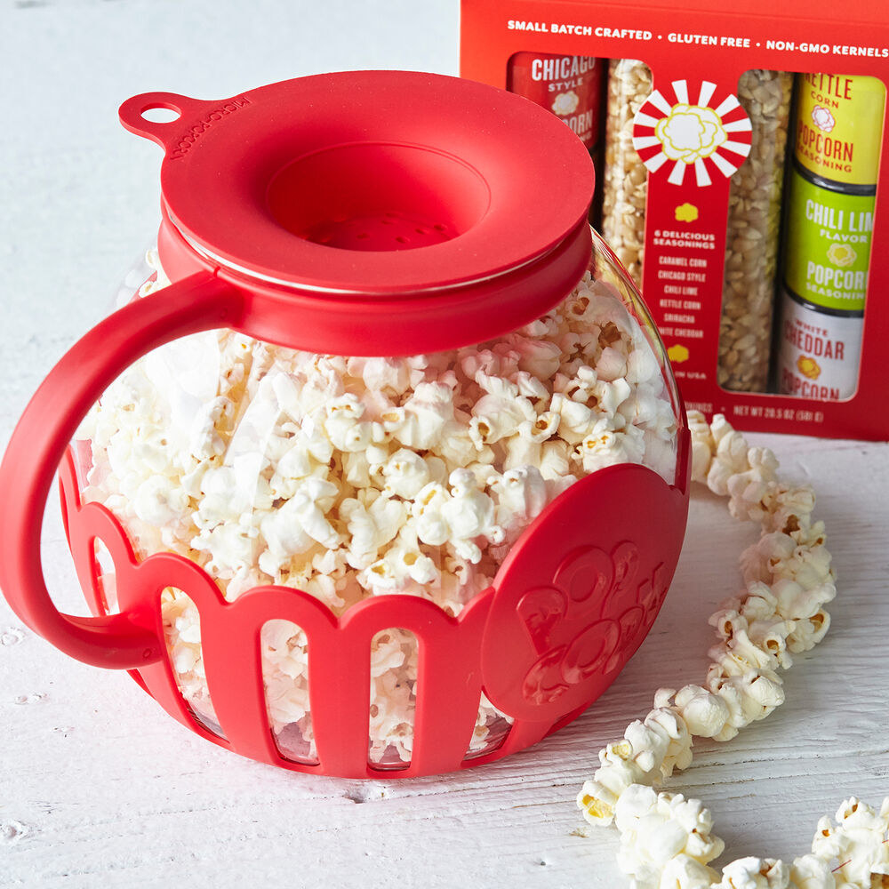 The popper filled with popcorn. It's a round glass vessel with a red silicone trim, indented lid, and handle that almost looks like a small pitcher