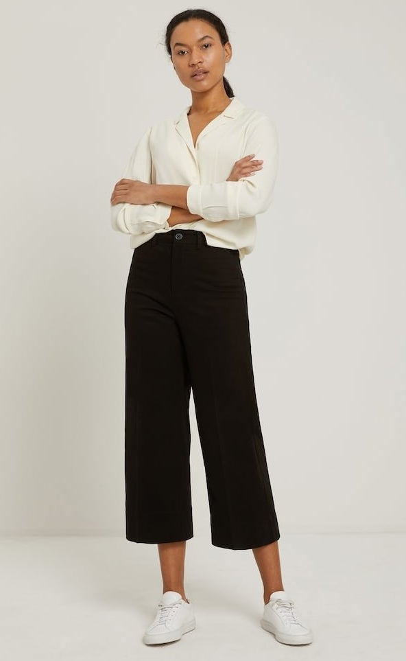 model in black wide-legged cropped pants with a cream button up and white sneakers