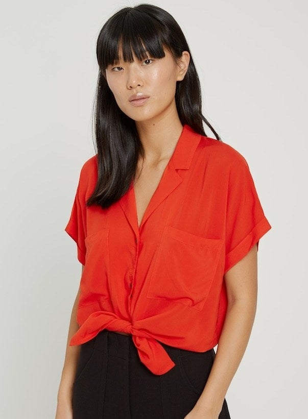model in bright red button-up blouse with short sleeves, a collar, and a large pocket on each side of the chest