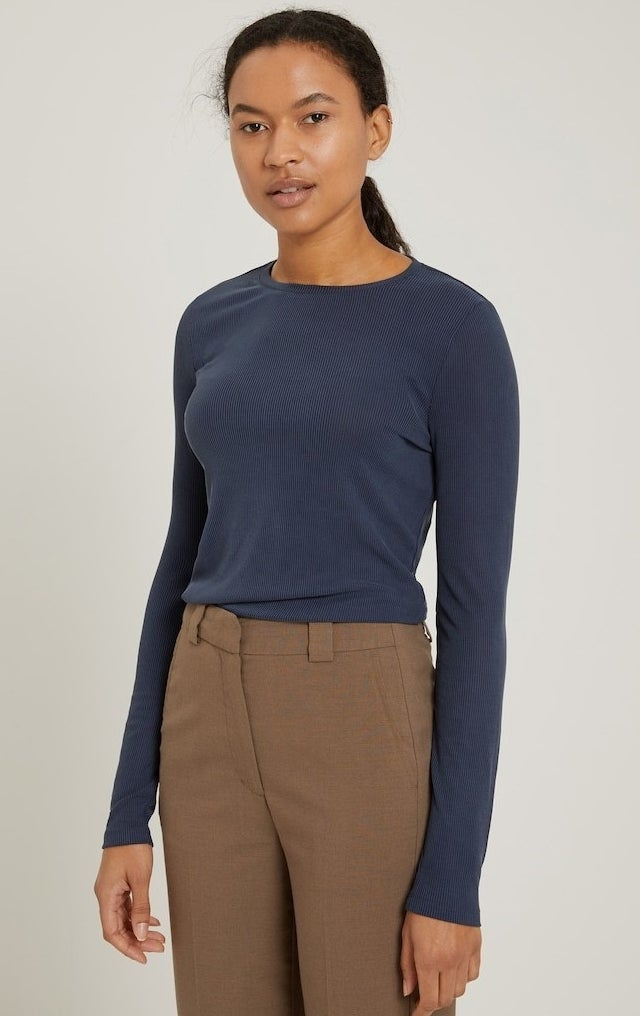 model in a navy long sleeve ribbed tee in navy tucked into brown trousers