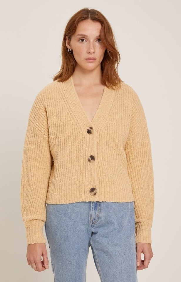 model in honey yellow v-neck ribbed cardigan with three large buttons styled with lgiht wash mom jeans