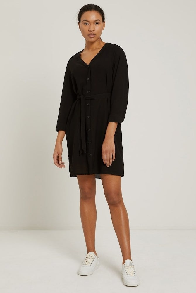 model in black v-neck dress with center buttons, a waist tie, and long sleeves that comes to the mid thigh, styled with white sneakers