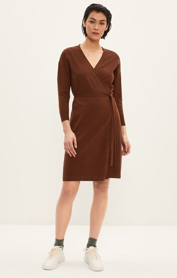 model in brown wrap dress with a v-neck waist tie and long sleeves, styled with with sneakers
