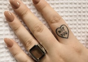 A tattoo on a pointer finger of a heart