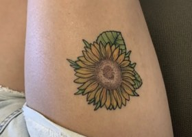 A yellow sunflower on someone's thigh