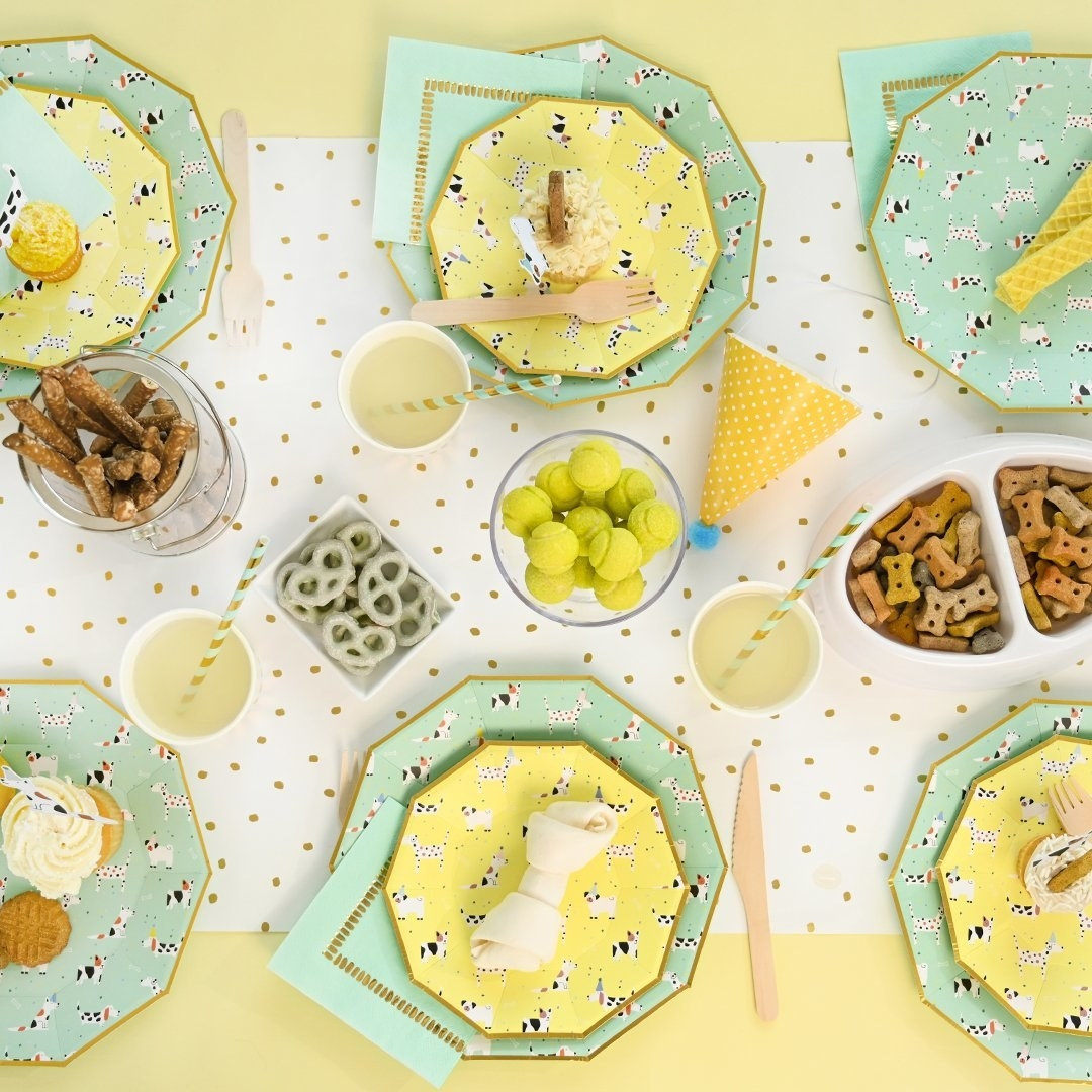 a beautifully decorated table for a dog birthday party featuring mint dog-covered plates, yellow dog-covered dessert plates, mint-colored napkins, and lots of dog treats