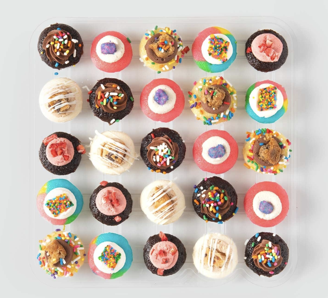 25 bite-sized cupcakes with frosting and tiny toppings in various flavors, packaged in a transparent plastic tray