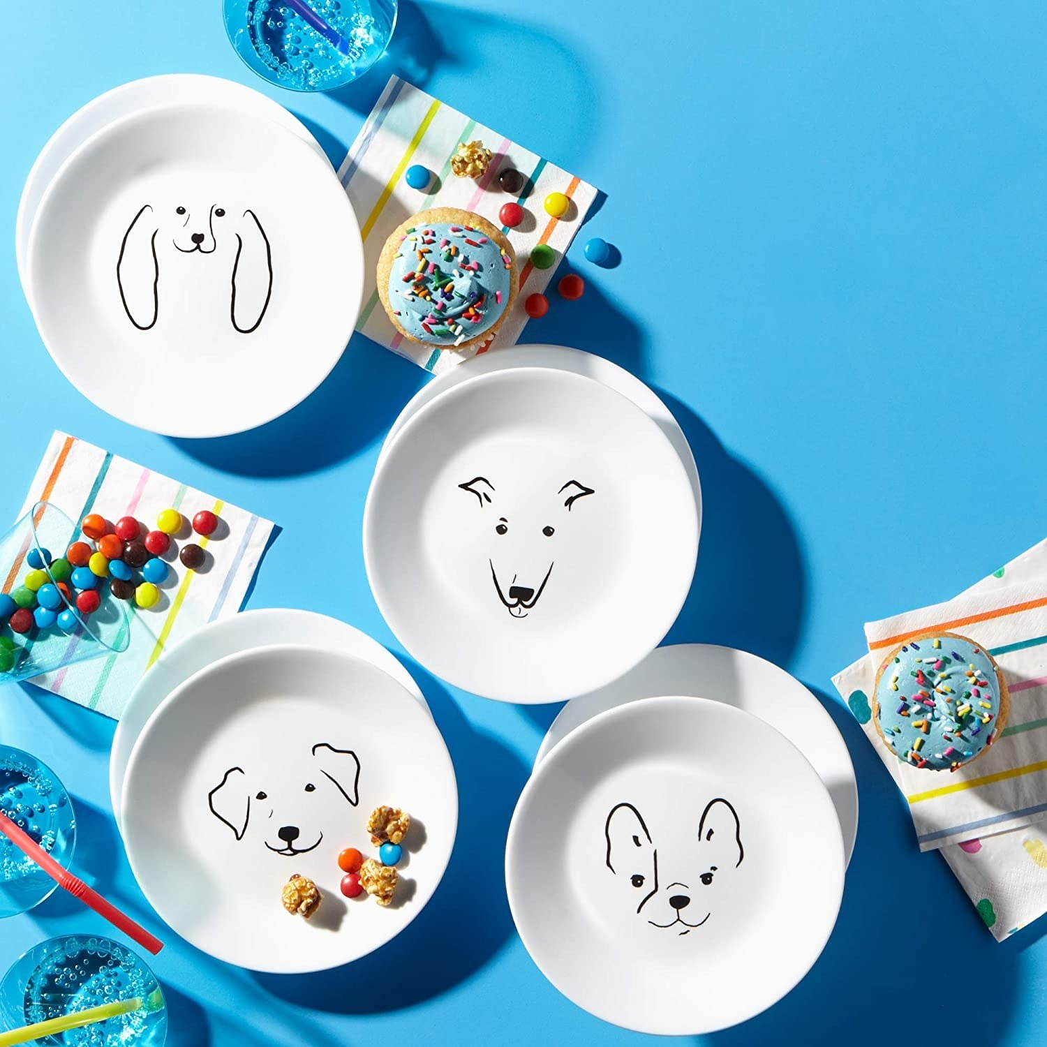four white plates with the outline of different dog faces on them in black sitting on top a bright blue dessert table