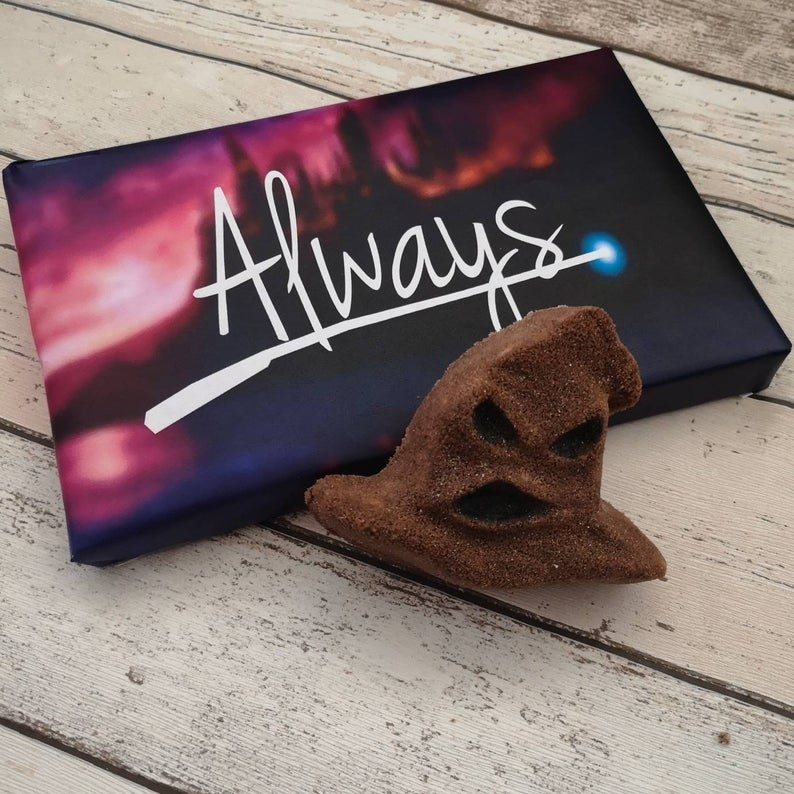 "The brown bath bomb in front of its packaging box that says ""Always"""