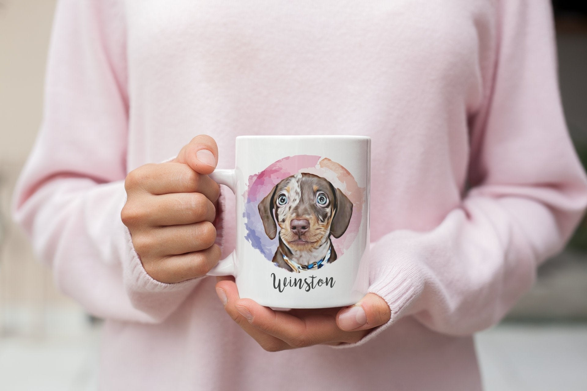 someone in a pale pink sweatshirt holding up a white mug with a water color painting of a dog with the dog's name under it in a script font