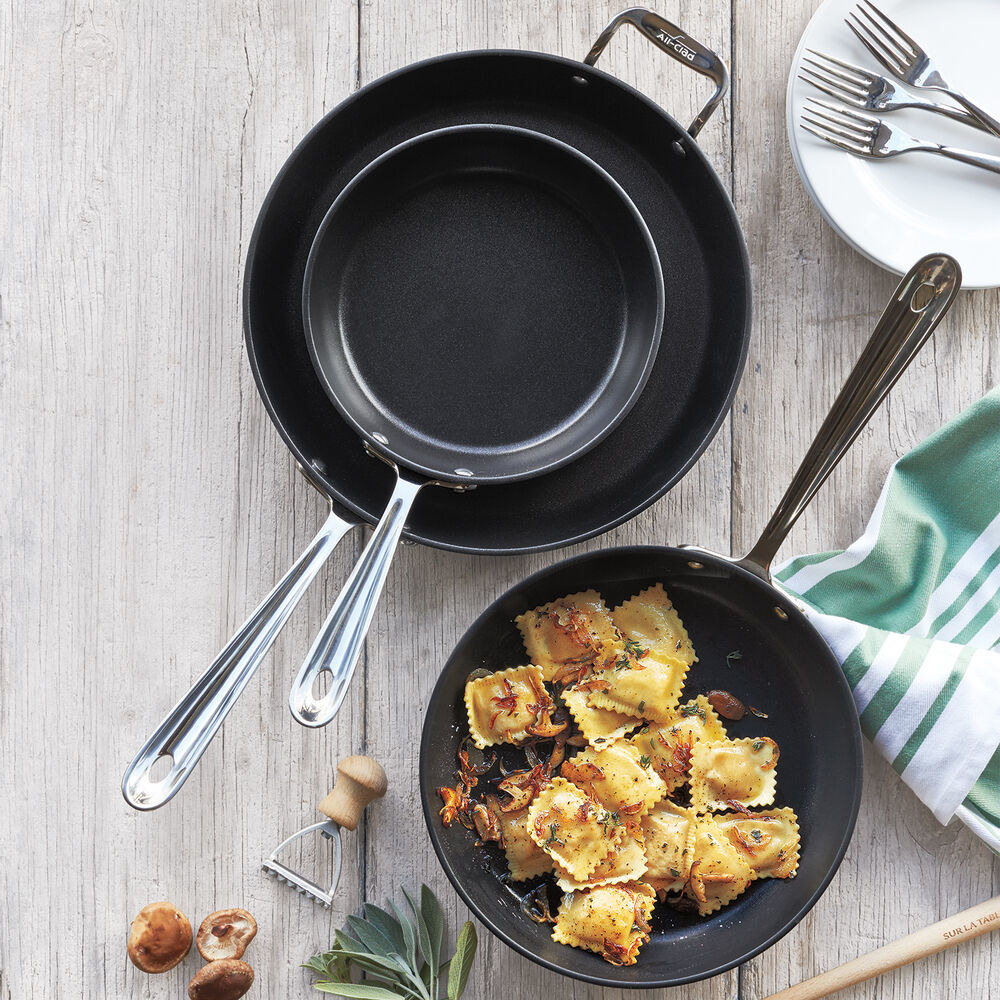 The smallest and largest skillets empty and stacked together next to the medium sized one, which is filled with ravioli