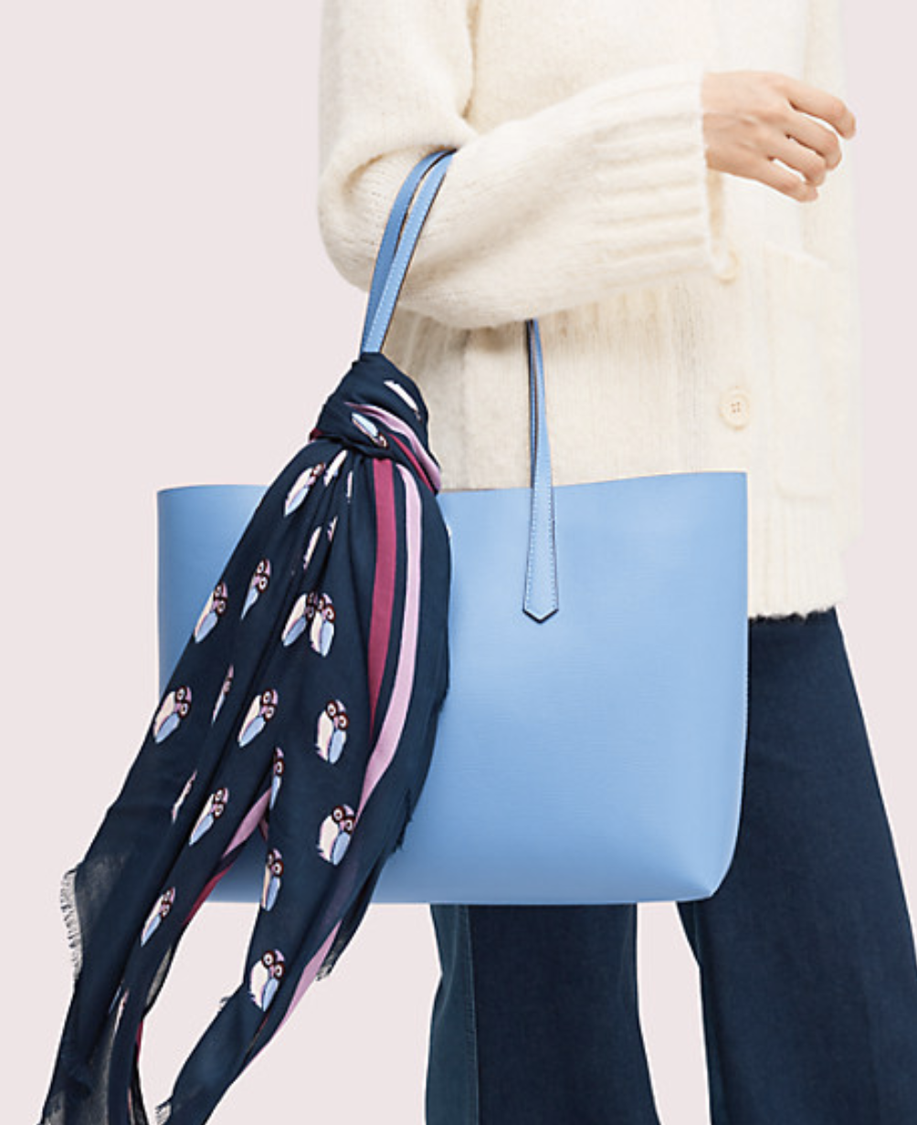 Model holding a handbag with the navy scarf with pink stripes and small blue and pink owl design tied around the handle