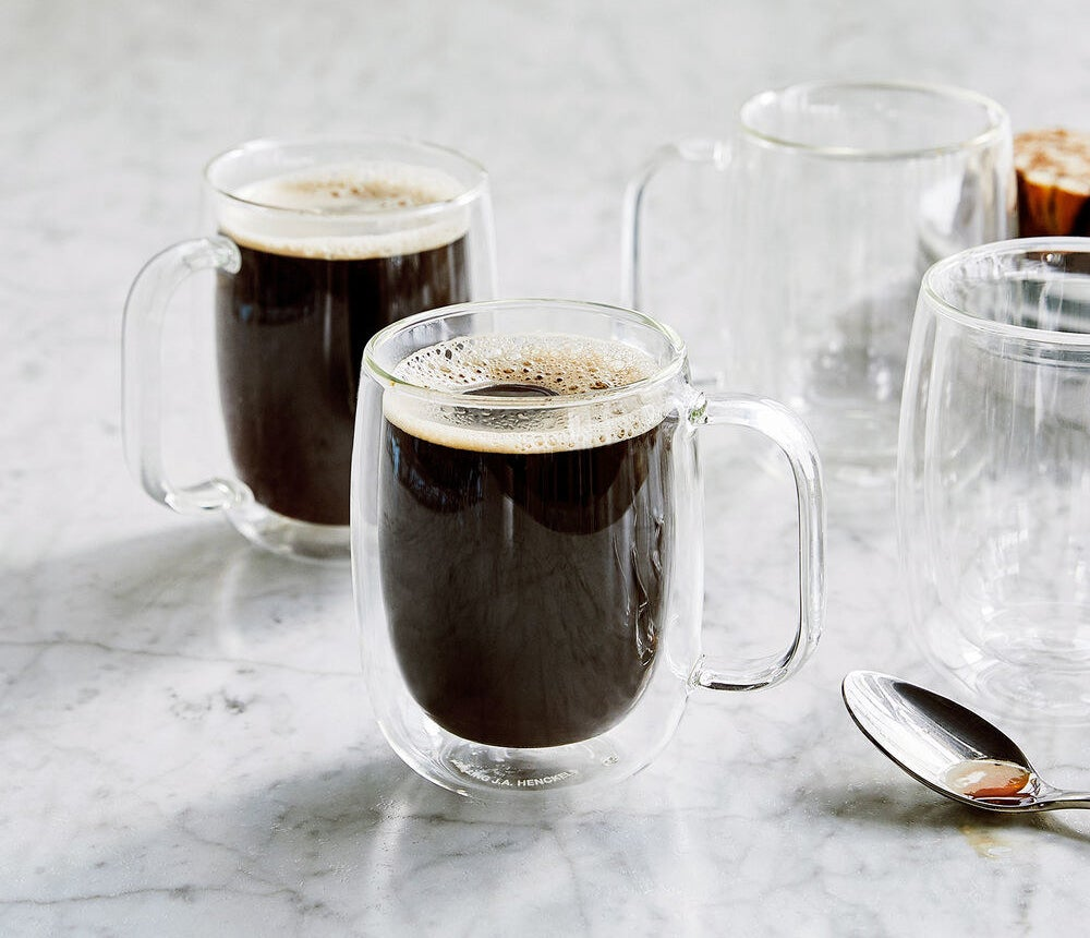 Two glass mugs filled with coffee, showing that one layer remains transparent even when the inner one is filled with liquid, creating a cool floating effect