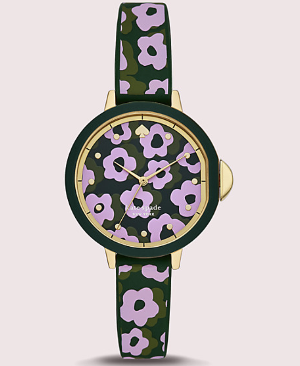 Closeup of watch with green face with purple and green flower pattern and the same color and pattern on the band