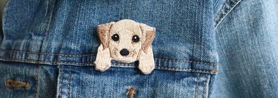 an iron-on patch of a pale colored puppy with big eyes seeming to hang over the pocket of a denim jacket