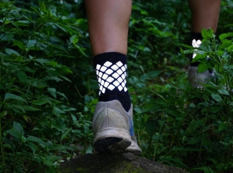 A person wearing the reflective socks while walking on a leafy path