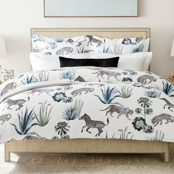 White bedding with water color style zebras, cheetahs, and tigers that are walking around several types of green and blue plants