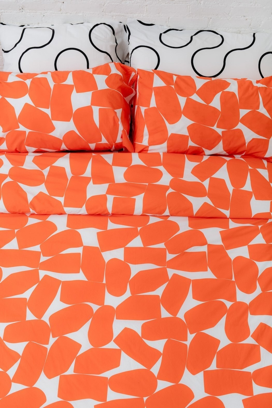 The bedding pattern has abstract rectangles in orange
