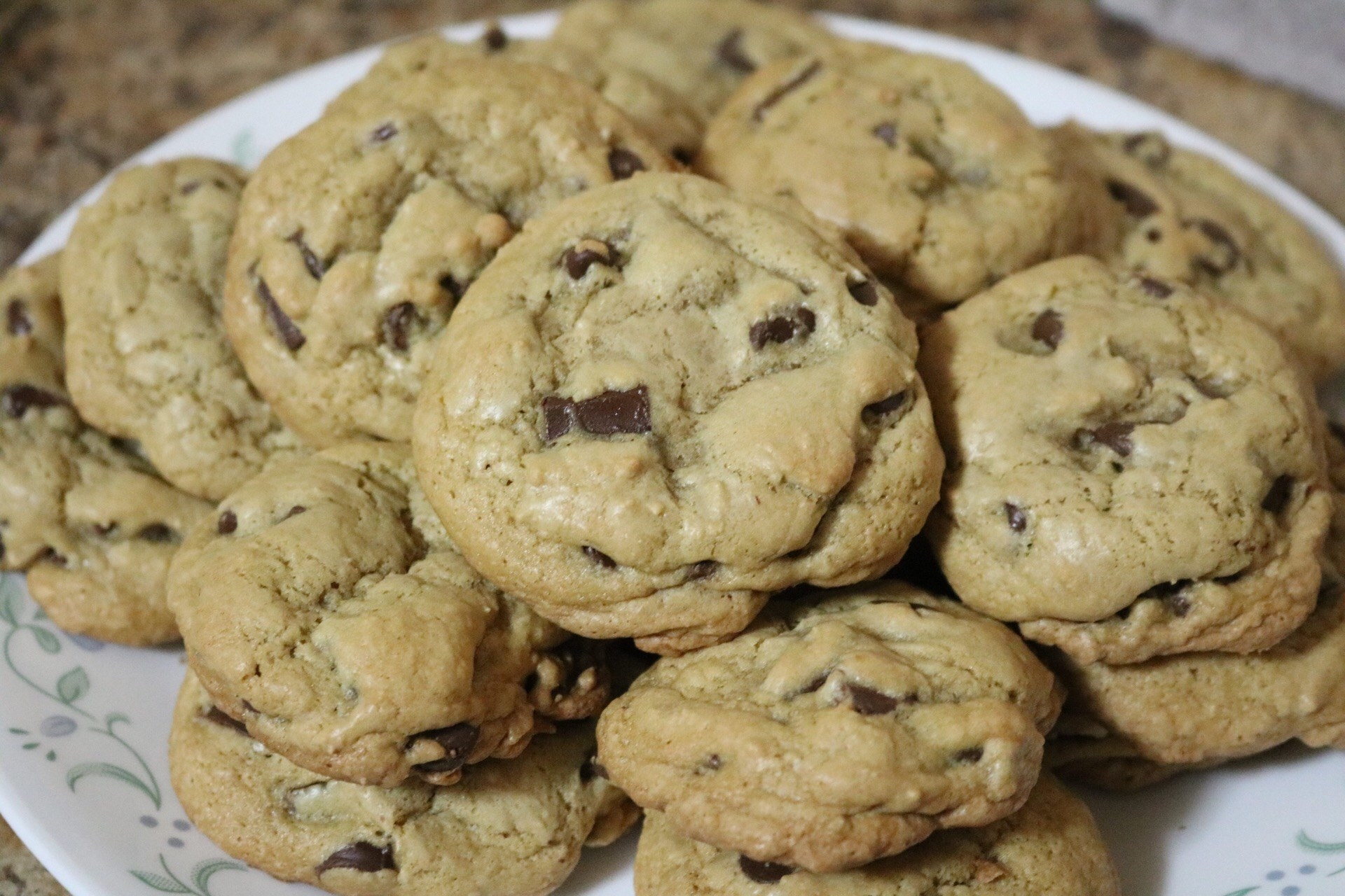 A plate full of fully baked cookies piled on top of each other
