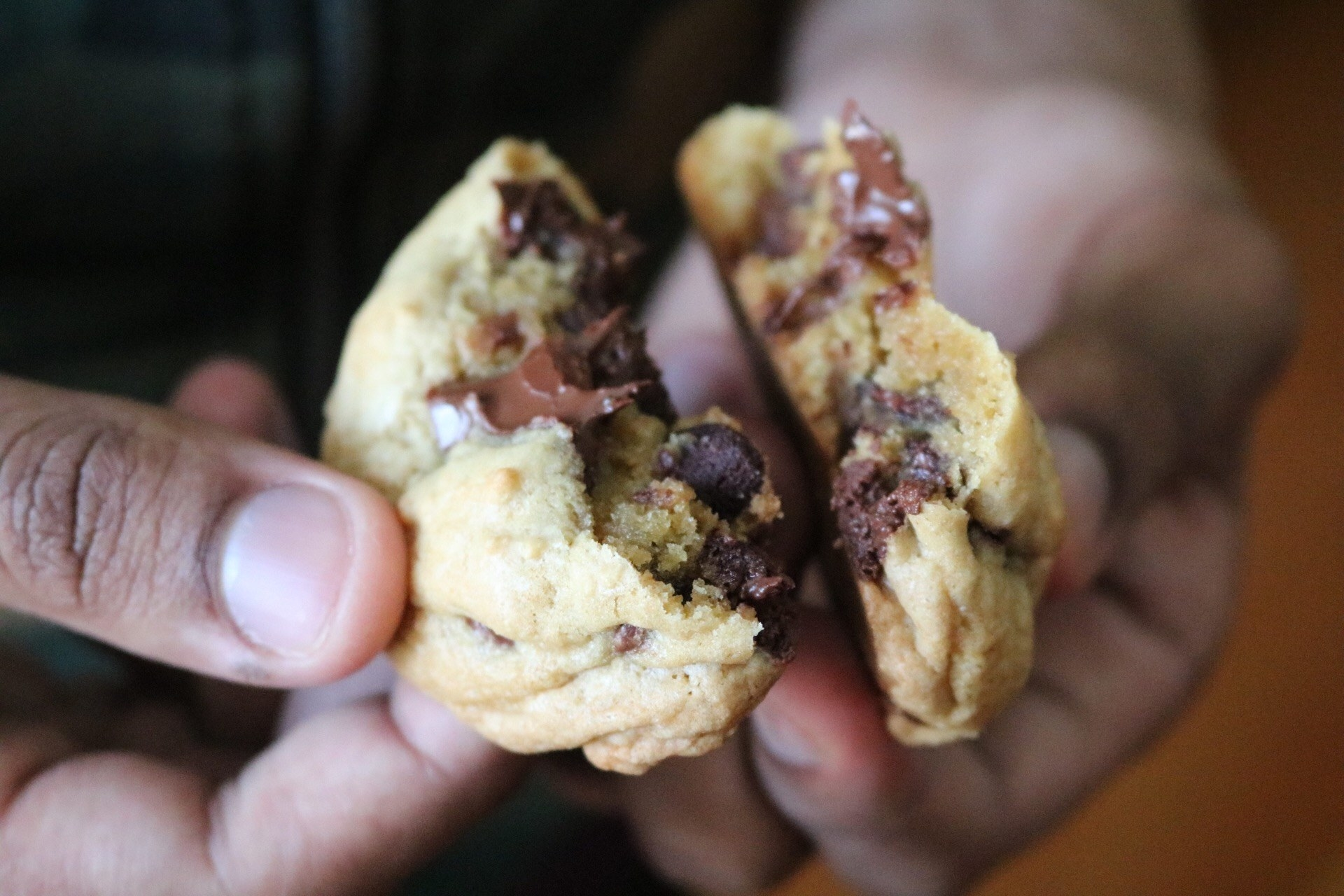 A cookie broken in half with chocolate chips inside and a gooey-looking melted chocolate chunk