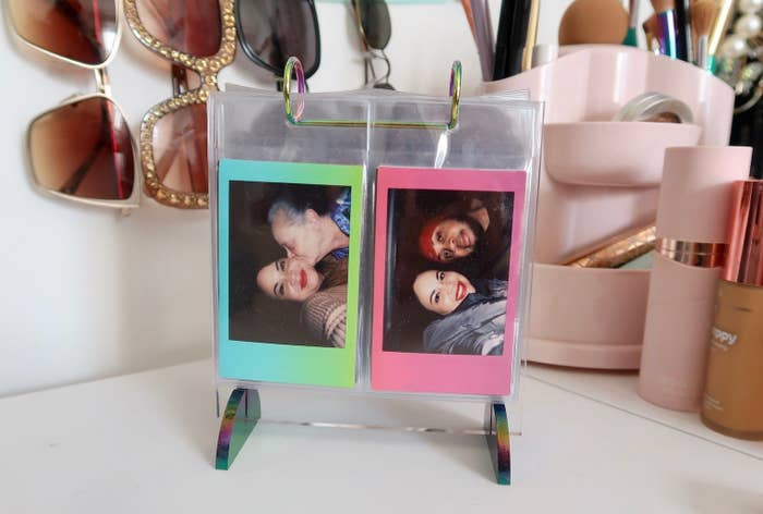 A photo flip book sitting on a vanity with a couple of family photos on display