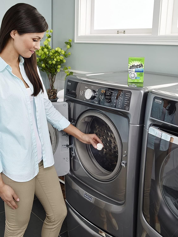 Una mujer echa una pastilla limpiadora a una lavadora