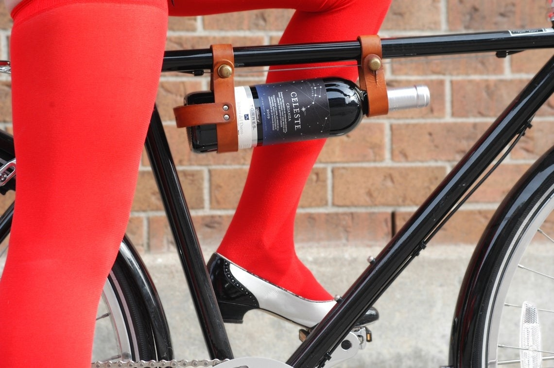A woman with red tights rides a bicycle with a bottle of red wine strapped to the top bar