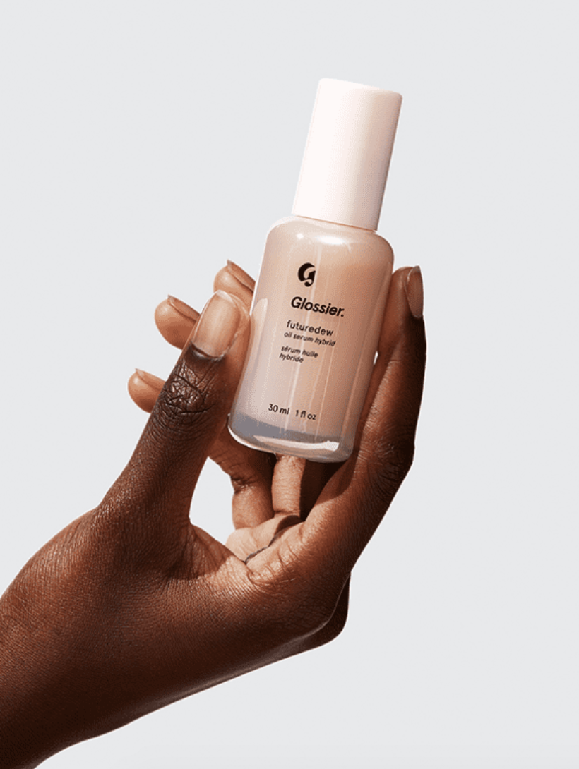 "A model holds a bottle that says ""Glossier Futuredew Oil Serum Hybrid"" in her hand"