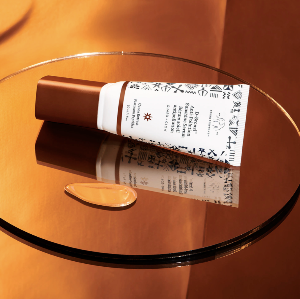 "A white tube that says Drunk Elephant's D-Bronzi Anti-Pollution Sunshine Serum"" in front of a brown background"