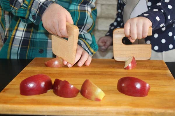Two children using wooden blocks with handles to cut apples