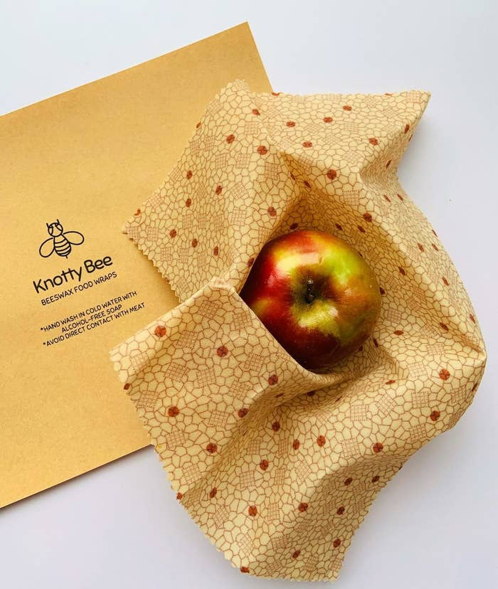 An apple nestled in beeswax wrap with a geometric pattern