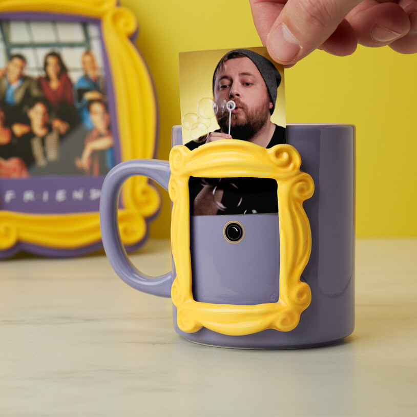 A person inserting a small photo into the signature yellow frame on the side of the mug