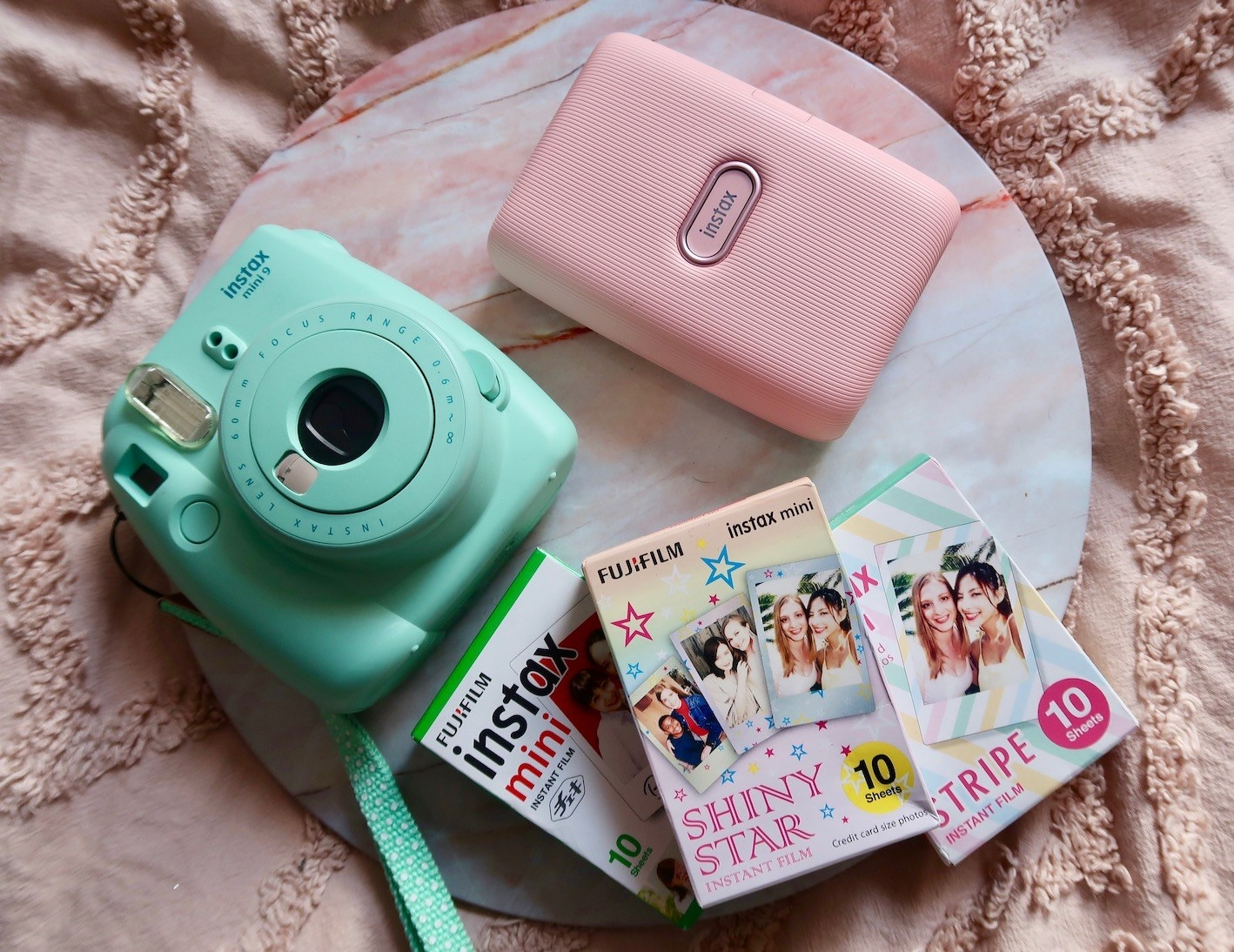 An instant camera, instant photo printer, and three packs of instant film on a surface
