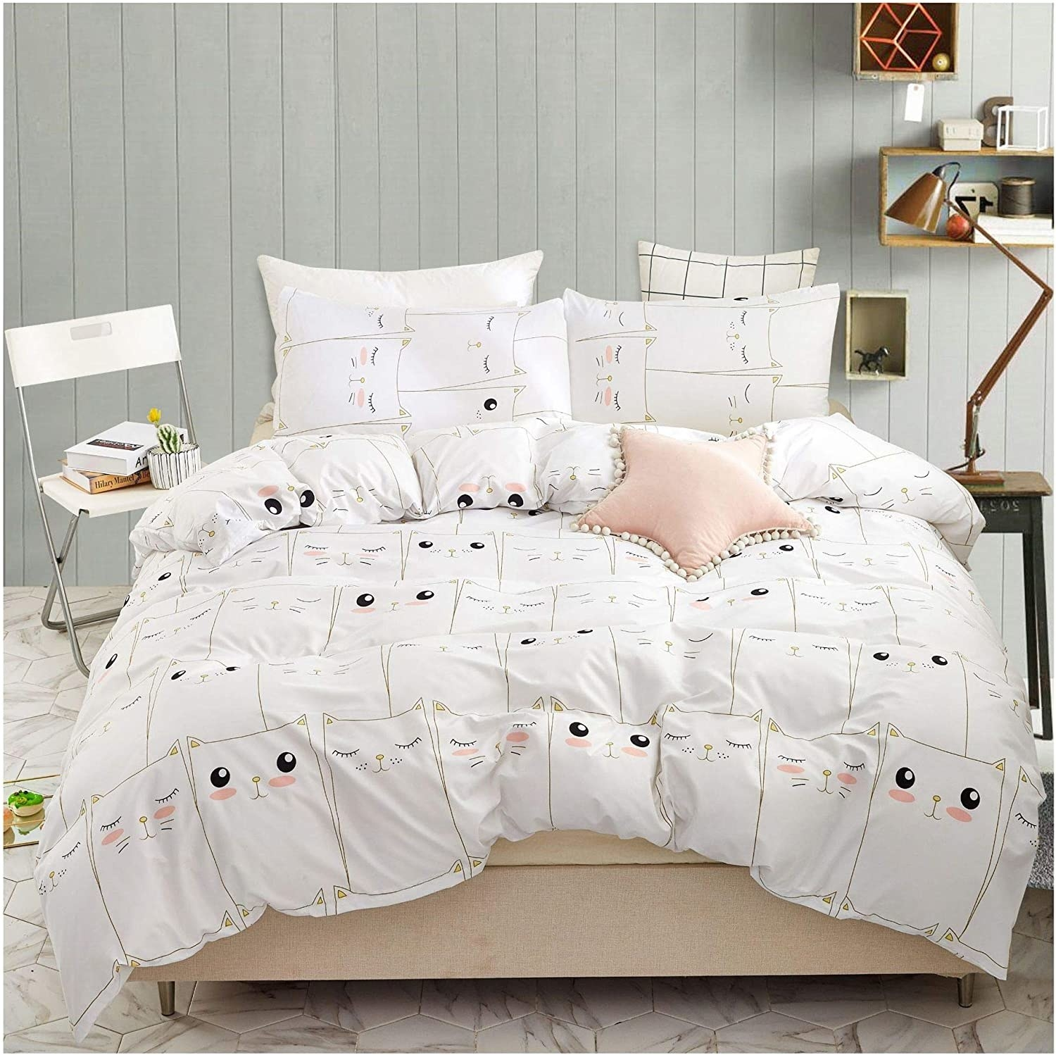 White bedding covered in simple cat faces; some have open eyes, closed eyes, and rosy cheeks
