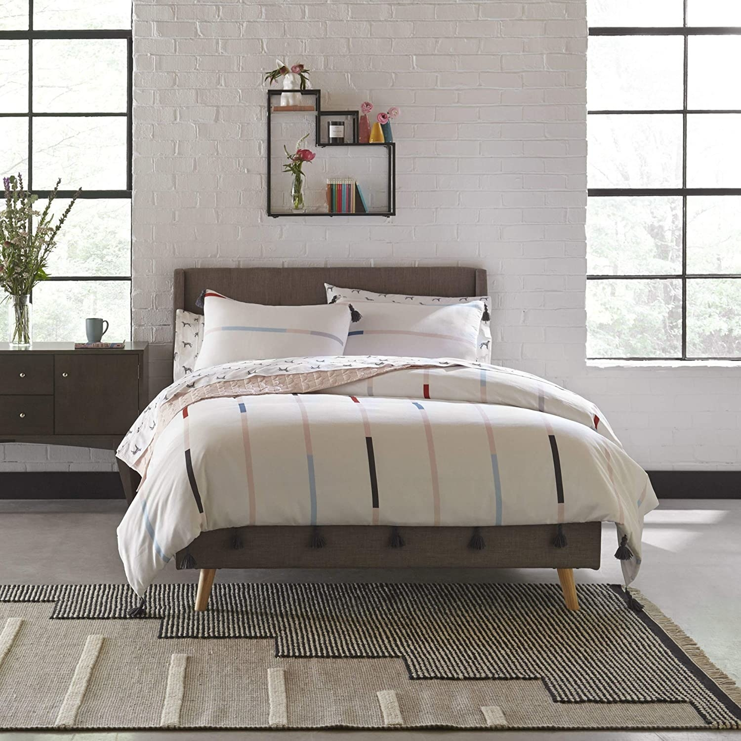 A cream bedding with multi-colored vertical stripes ending in black tassels