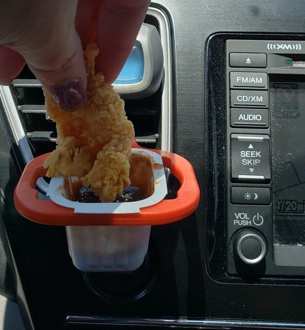 A person inside a car dipping a chicken tender into a sauce packet held in place by the dip clip, which is attached to the AC vent