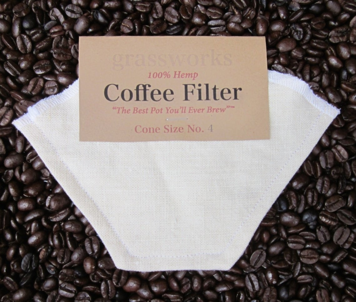 """A white cloth coffee filter on top of coffee beans that says """"100%hemp coffee filter the best pot you'll ever brew cone size 4"""""""