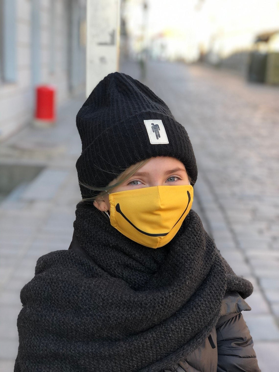 A person wears a bright yellow mask with a huge black line in the shape of a smile printed on it