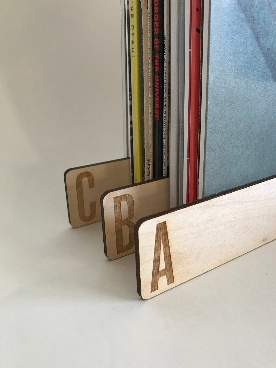 A stack of records with three wooden dividers with engraved letters on them