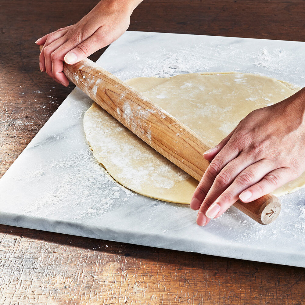 Hands using a rolling pin rolling dough on the board