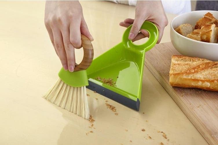 Una personas acumula migas con un cepillo pequeño y luego las echa a un recogedor