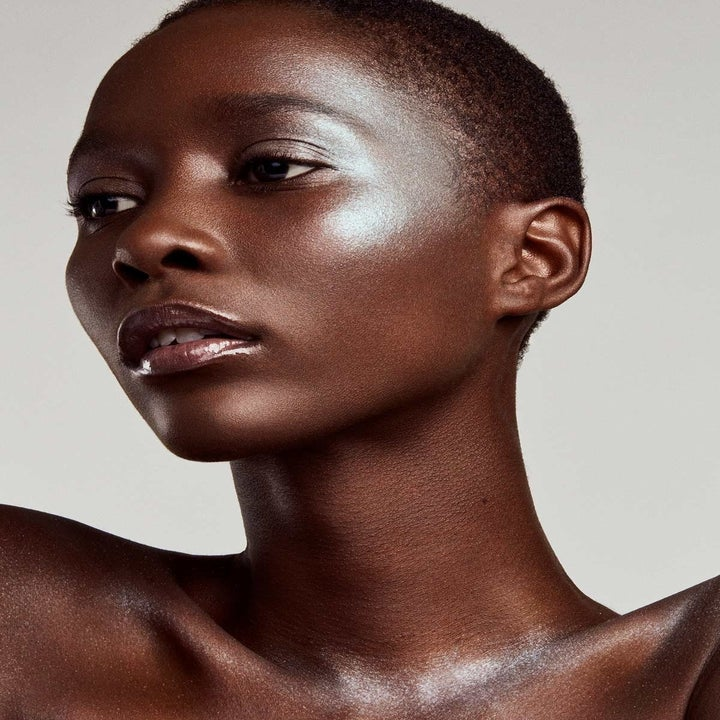 model with dark skin wearing the highlighter in ice blue